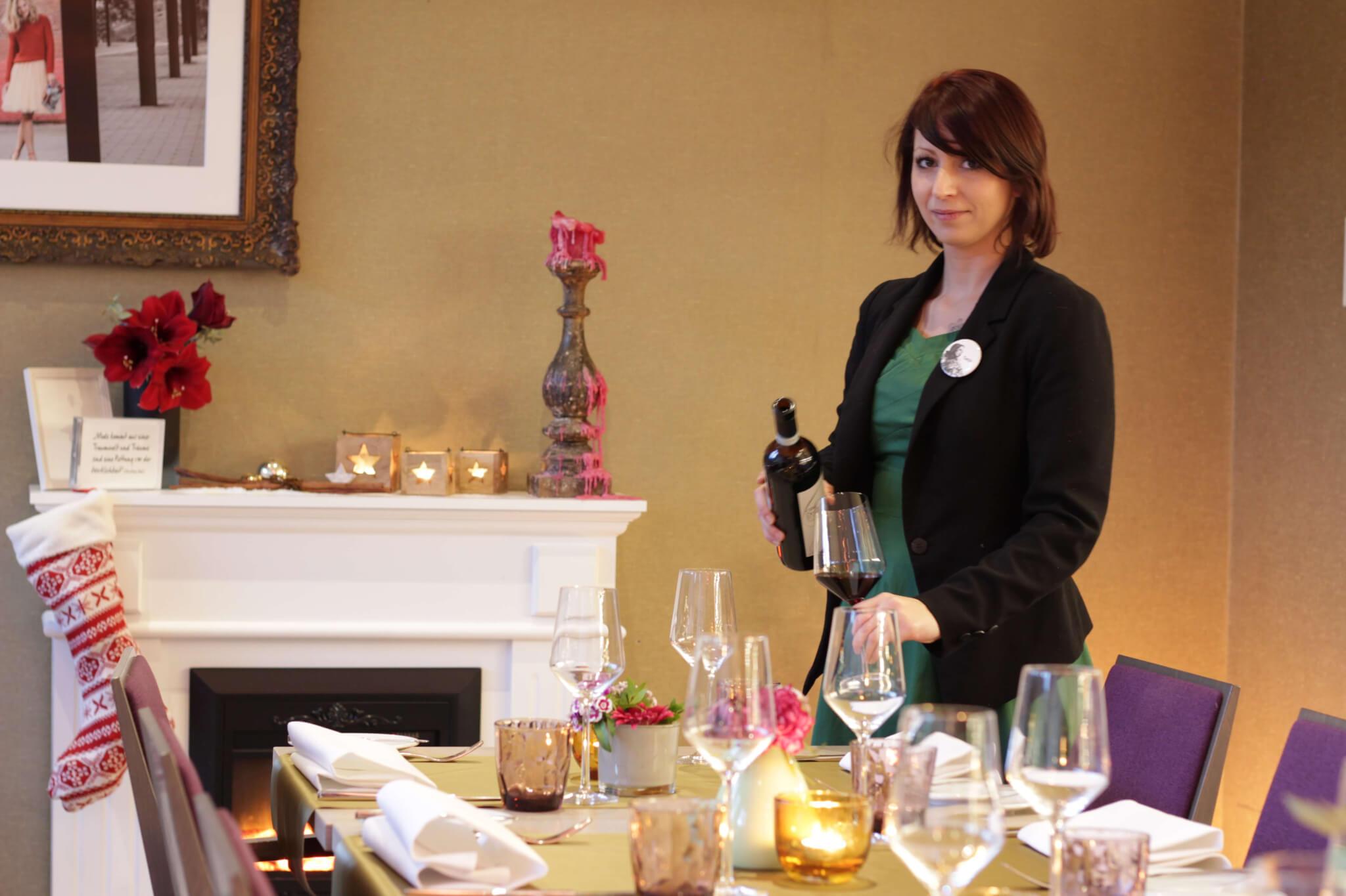 gedeckter Tisch mit Tanja Wein ausschenken